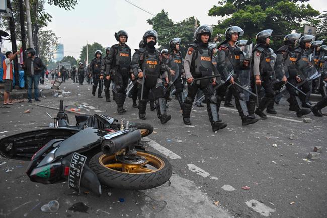 示威现场一片凌乱,一辆摩哆翻倒在路上,警员拉大队清场。(法新社)