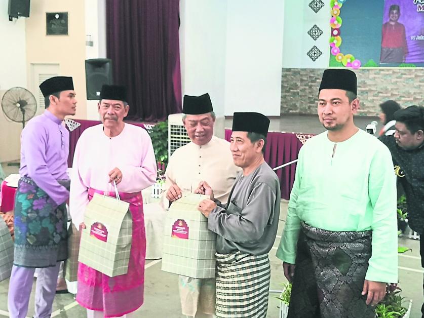 慕尤丁(左3)在沙鲁丁嘉马(右)陪同下,颁发恩物给朝圣者,以表达最深的祝福。