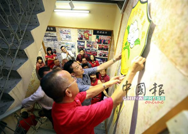 """邹尚轩(左)联合谢琪清,把森茶阳会馆的模型徽章贴在""""历史足迹""""。"""