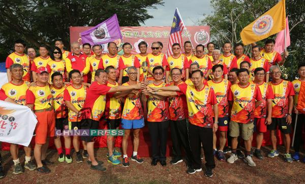 钟来福(前排左2起)和方天兴移交火炬给三宝山跑跑会。