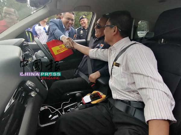 阿德里(左)分发杂锦粥给驾驶人士。