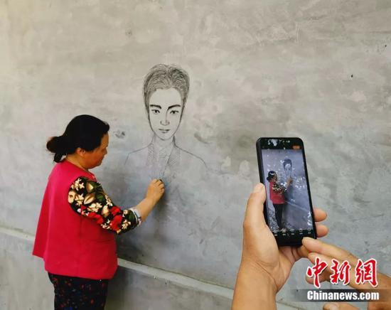 丁春梅墙上作画。