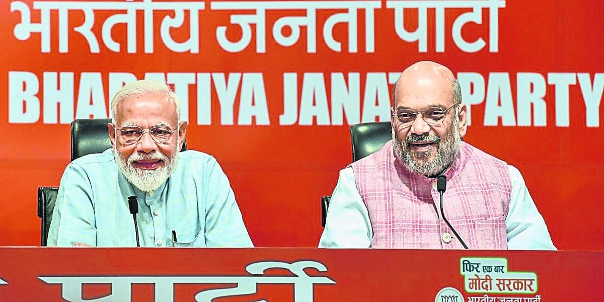 莫迪(左)召开上任5年的首个记者会,但对记者的提问一概不答,都交由其身边的印度人民党主席沙阿代为回答。