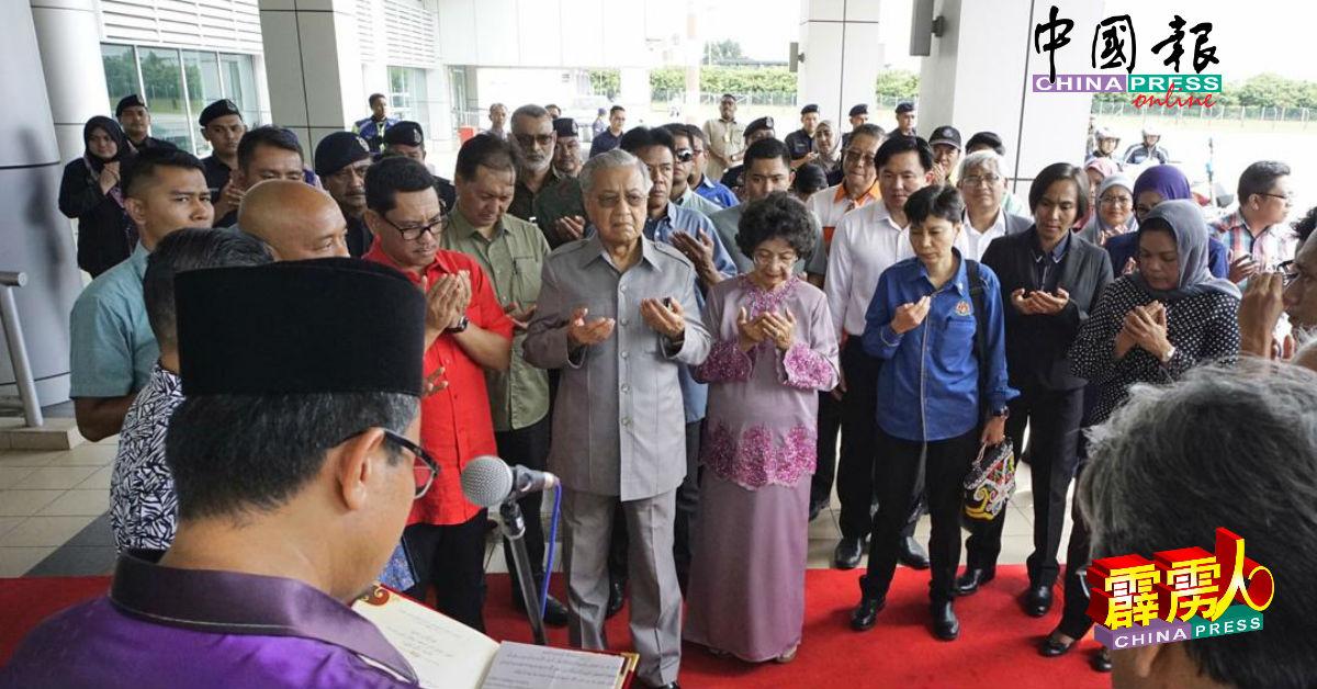马哈迪(右4)和西蒂哈丝玛(右3)抵达怡保苏丹阿兹兰沙机场后,进行祷告仪式。