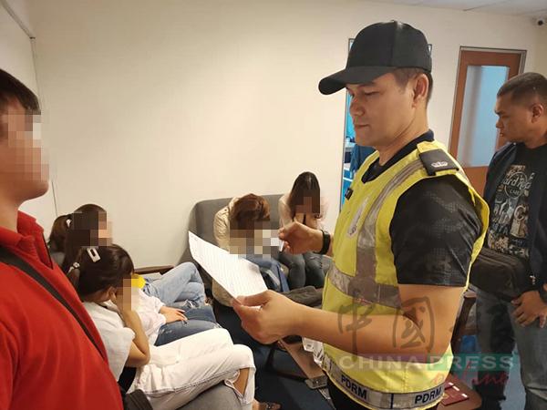 阿兹米(中)正在盘问华裔看场。