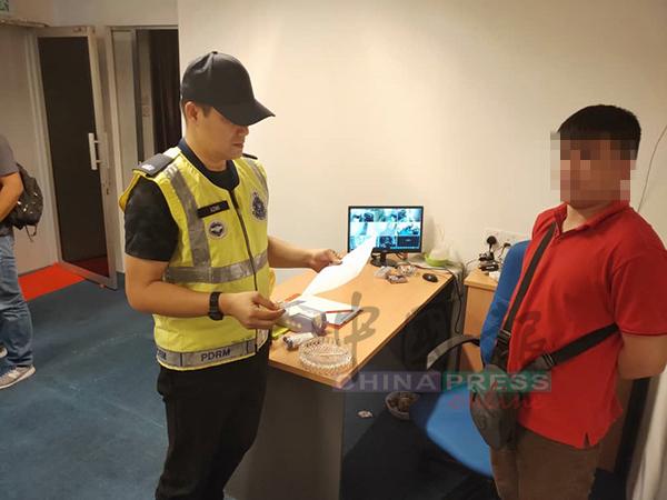 阿兹米(中)正在检查华裔看场出示的文件。