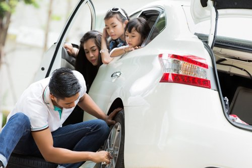 Father was to change the tire because the tire was leaking park beside the mother and children cheering
