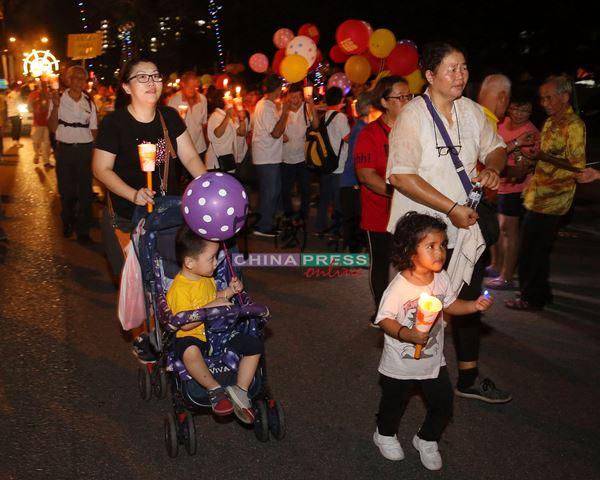 家长带同孩子参与游行,不惜推车步行,让孩子感染游行的祥和气氛。