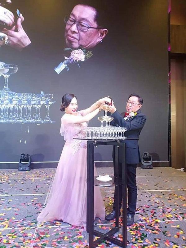 凯儿笑得合不拢嘴,与老公拿督戴华昌一同高举香槟倒入杯中。