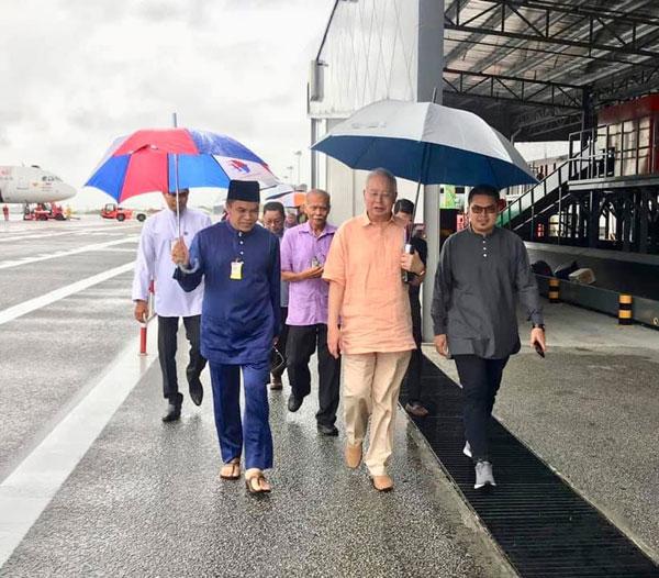 纳吉(右2)抵达浮罗交怡国际机场后,就下起雨来,他们撑伞进入机场内。
