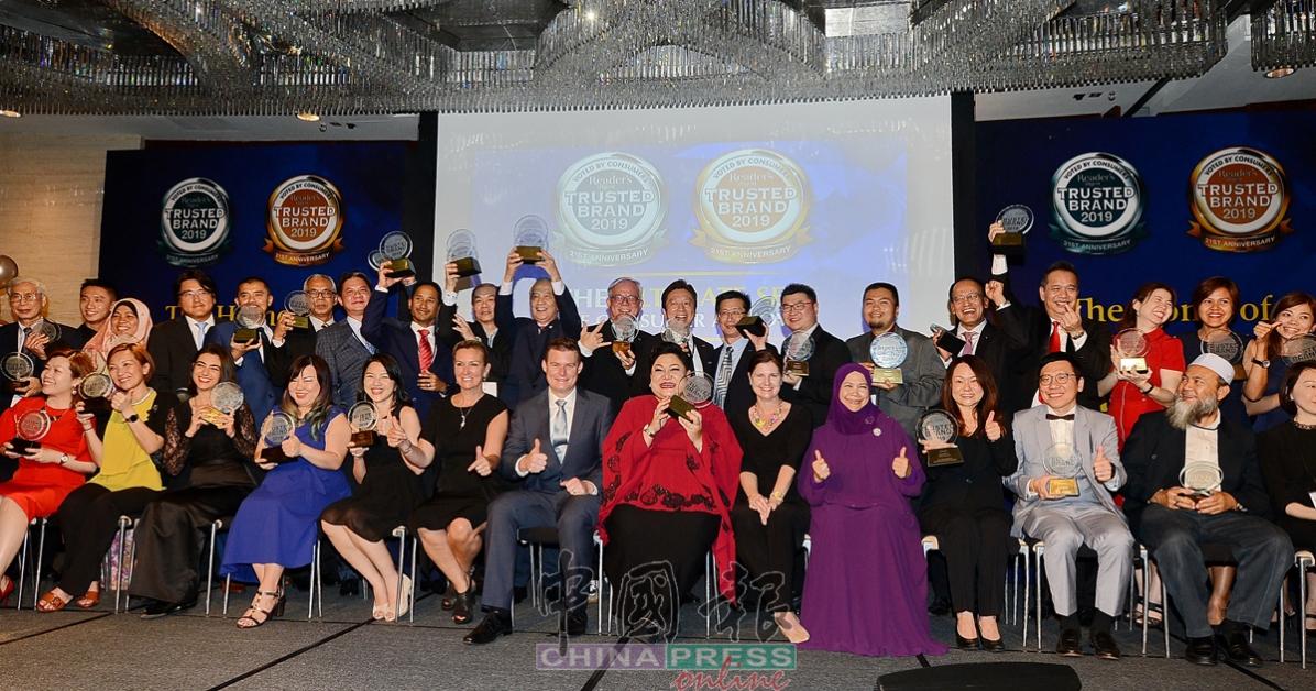 2019年《读者文摘》最受信任品牌得奖者在台上拍大合照时,开心展示奖牌。右6起为路易斯华特生及阿迪峇诺。