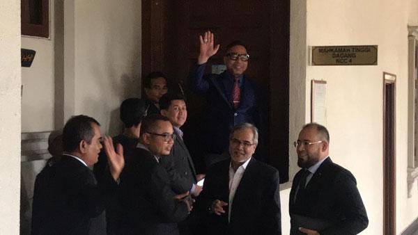 凯鲁丁(后者)步入法庭前,向媒体招手示好。