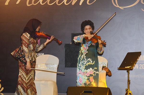 西蒂哈丝玛(右)在台上演奏小提琴。