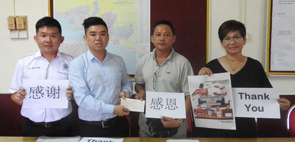 许家勋(左2起)移交筹获的款项给王文胜,左为罗明亮,右为傅秋霞。
