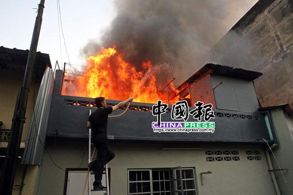 在消拯员还未到火患现场前,一名见义勇为的公众使用水管来扑灭大火。