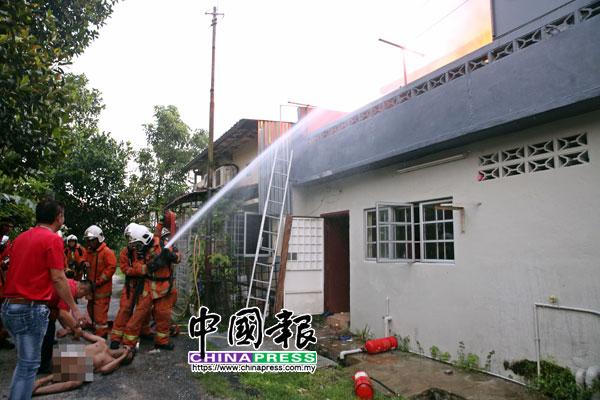 赤裸的男租客背部被灼伤,被救出后躺在地上等候救护车,而一旁的消拯员则忙着扑灭火势。