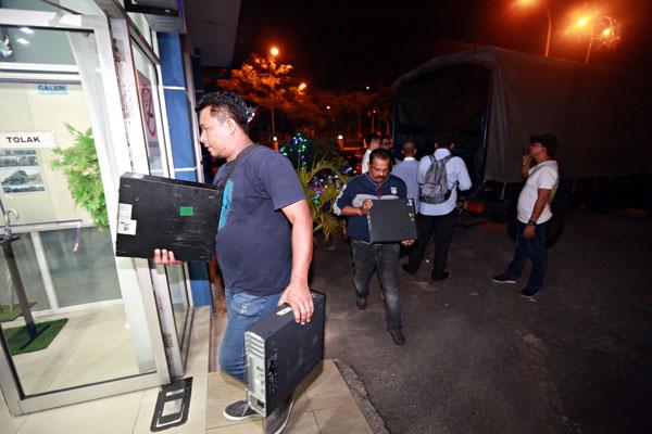 警员把起获的电脑工具搬入警局,作为证物。