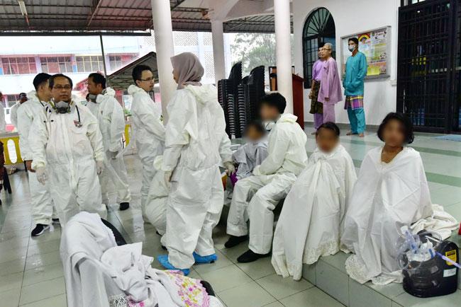 受影响的学生坐在学校附近的清真寺,等待消拯员帮忙冲洗身体消毒。
