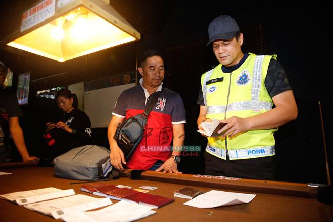 阿兹米(右)正检查落网外籍女郎的护照。