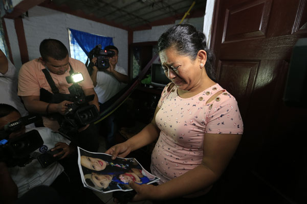 罗萨看着儿子拉米雷斯和媳妇阿巴洛斯和照片,一边流泪。(美联社)