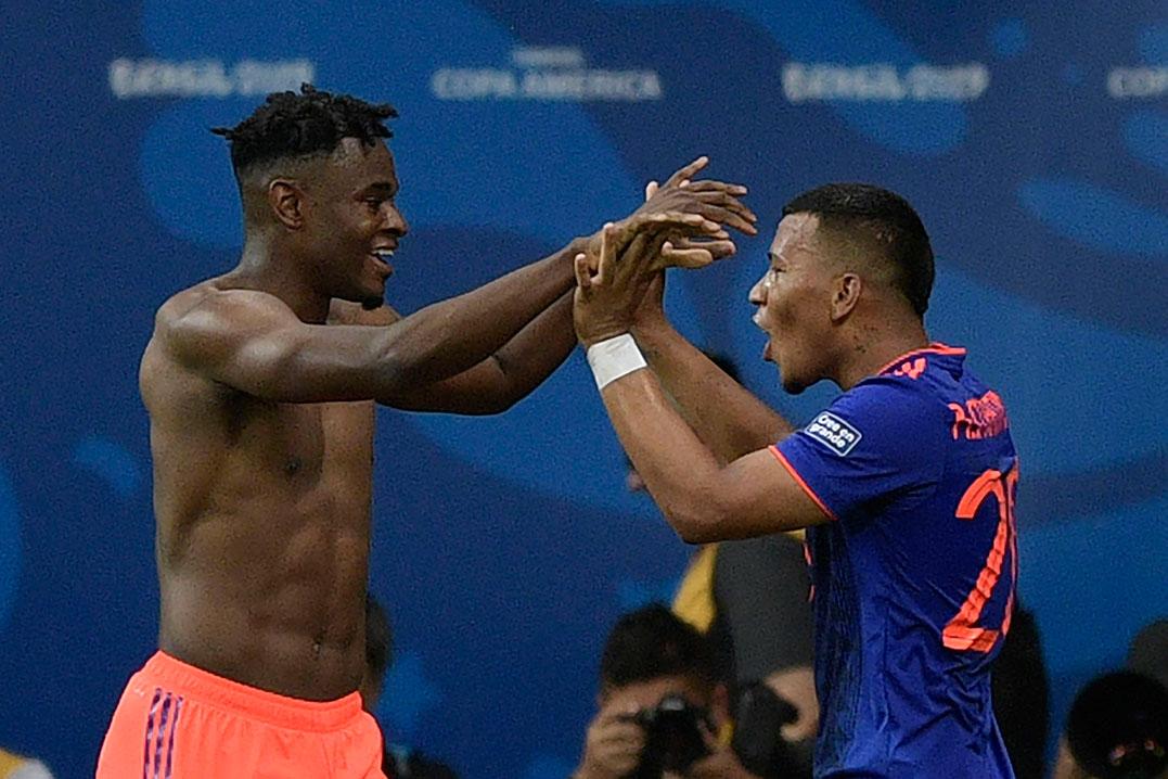 D.萨帕塔(左)为哥伦比亚锁定胜局后,与首开纪录的马丁内斯一起庆祝。(法新社)