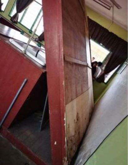 科学室的厚重黑板倒塌,刚好压着在教书的老师。(图取自光芒日报)