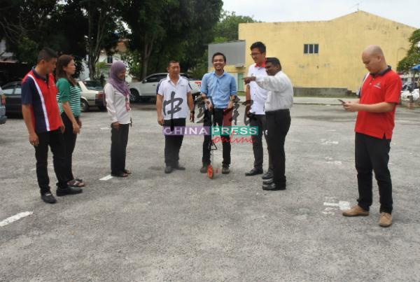 工作人员为新马六甲花园早市路段测量面积。左起为洪清顺、萧丽燕、卡迪、卓财贵,右起为温金源、纳登、谢守钦。