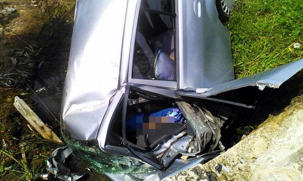 车祸发生后,肇祸轿车车头严重损毁,死者被夹在车内。