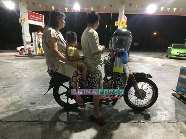 刘记福(右)及郑佩妹(左)带着孩子共乘摩哆到油站及咖啡店捡铝罐。