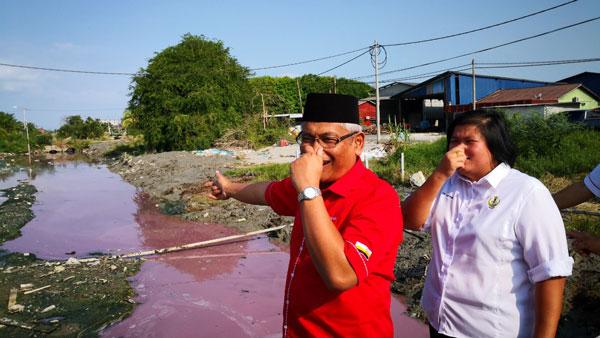 阿都阿兹巴里(左起)和林小玉,难忍河沟发出的恶臭。