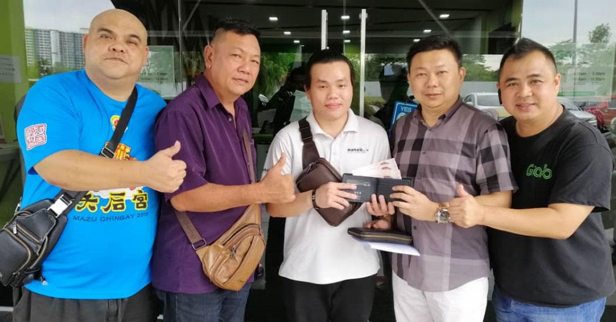 陈万兴(右2起)代为领取许政雄转交的东马闻人皮包。左起为萧锦坤、罗先生和张永顺。