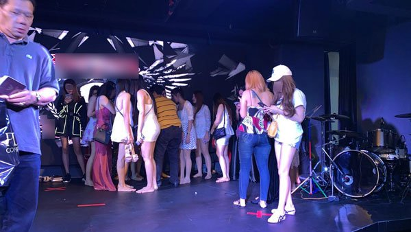 衣着性感的陪座女郎聚集在舞台上,等候警方发落。