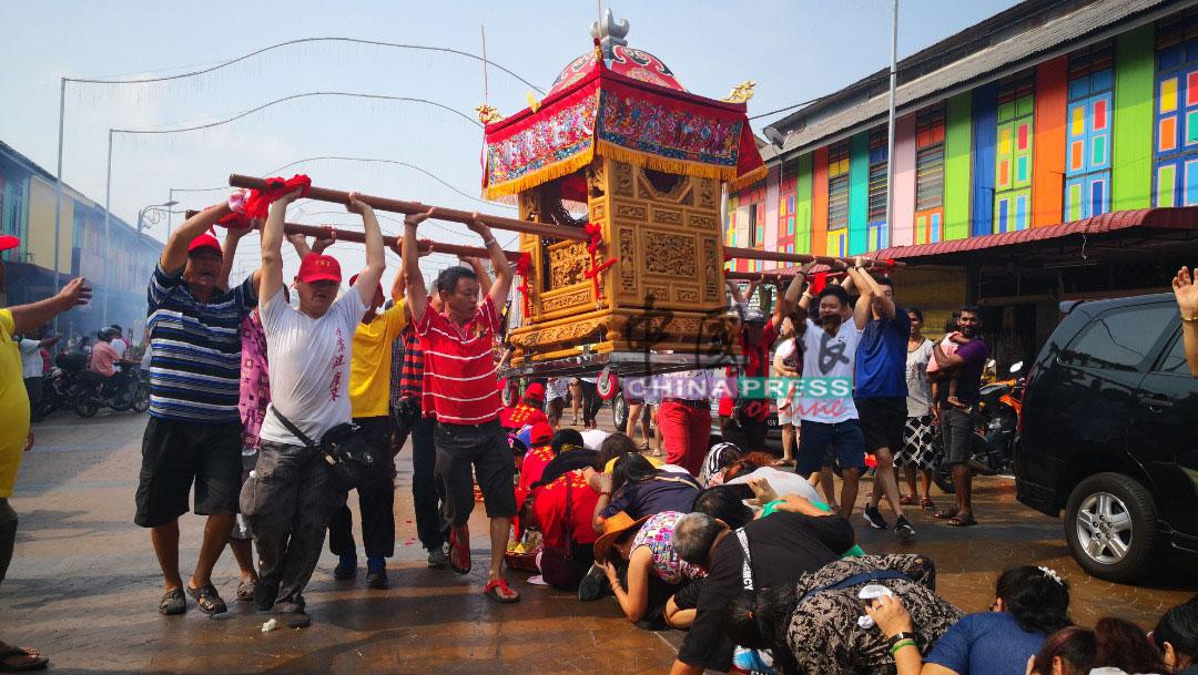"""善信纷纷跪列成""""地龙""""形式,让多人联抬的逾200公斤大銮轿,从头顶跃过祈福。"""