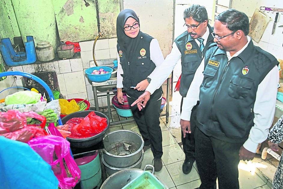 威拉班(右)和卫生局执法官员,检查厨房卫生是否达标。