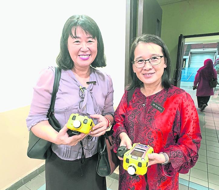 庄秀云(左起)及林慧梅代表学校领取气体分析仪器,并透露校方每天必须汇报4次空气素质数据给有关当局。