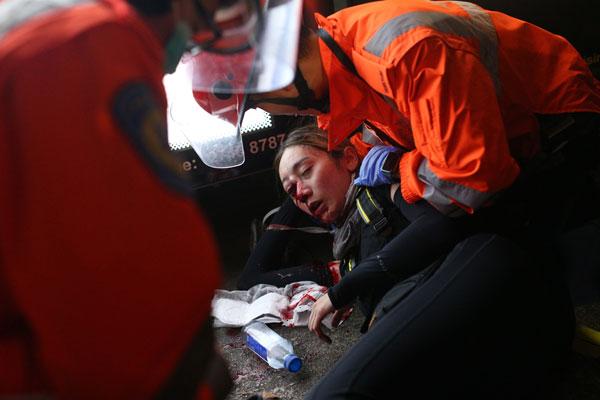 一名年轻女子眼部疑被布袋弹所伤,救护人员在现场帮该名女子急救。