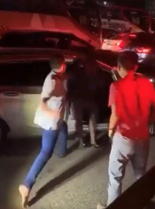 身穿蓝裤男子向轿车司机头部挥了一拳。