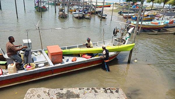 渔夫赛夫在海上寻获独木舟后,用渔船载回码头。(受访者提供)