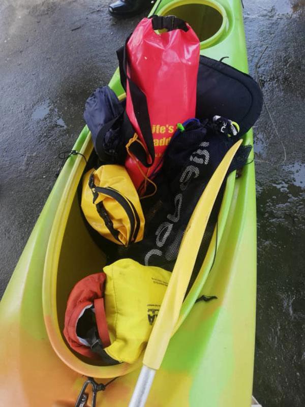 家属在彭加梦码头认领独木舟上的随身物品。