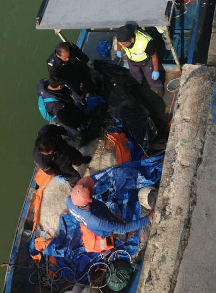 在瓜拉甘马挽岸外发现的一具女尸,运抵海事执法局码头。
