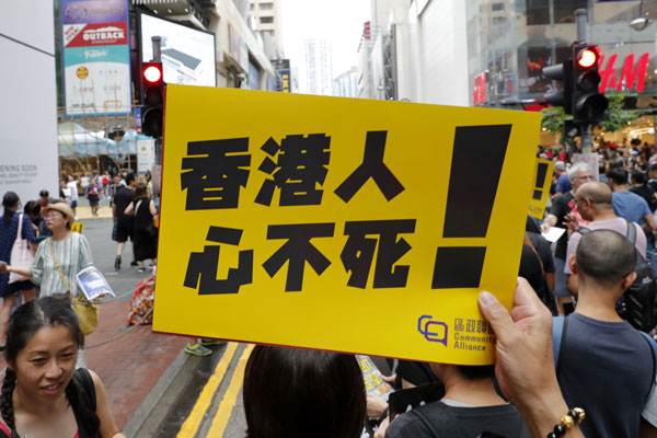 """有民众在周日的集会上手持""""香港人心不死""""字牌。(美联社)"""