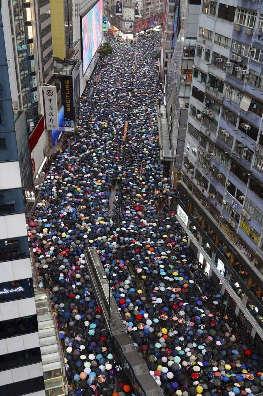 香港周日再发起大型游行,大批身穿黑衣的民众撑起雨伞在香港街头游行。(美联社)