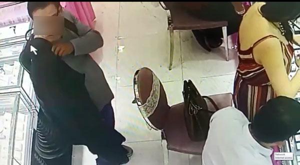小偷伺机靠向华妇身后,企图偷手提袋。
