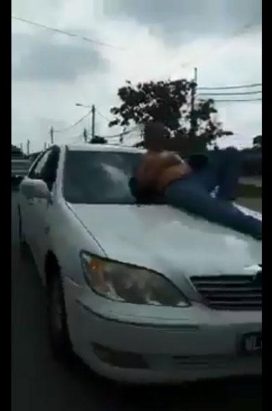 """赤裸上身的男子躺卧在轿车前挡风玻璃上""""兜风""""。(图取自网络视频截图)"""