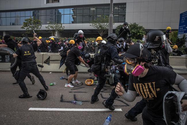 在周六举行的观塘游行中,示威者与警方发生冲突。(欧新社)