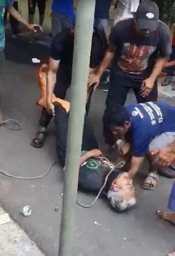 男子被牛踢了一脚后,痛苦倒地。