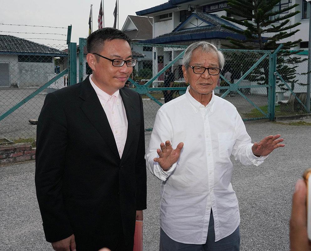 官有缘(右)在梁卓经陪同下,摆动双手指不宜发表任何言论。
