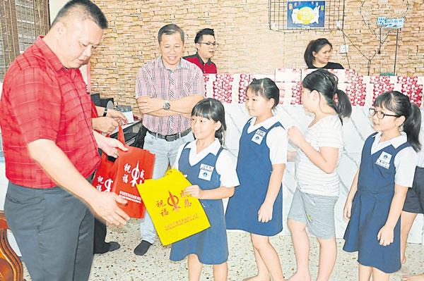 吴金财(左)派发月饼给筑梦号工作坊的学生。