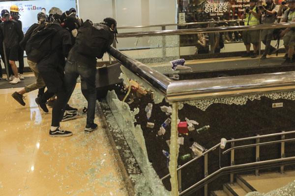示威者砸烂一个商场的玻璃围栏。