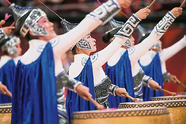 穿着古装衣服的舞蹈员,在球场上表演余兴节目。(法新社)